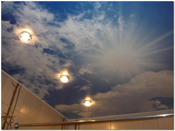 Глянцевое натяжное полотно из ПВХ-пленки с софитами в ванной комнате